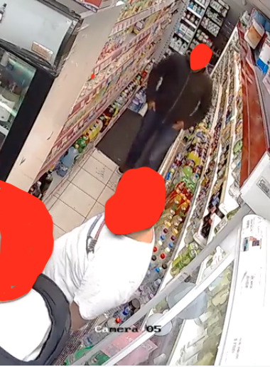 Man in hoody shown walking casually in small shop. Second man in white t-shirt stands talking to police officer.