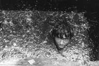A Mumbai street cleaner up to his neck in a drain (Photo © Sudharak Olwe 2003)