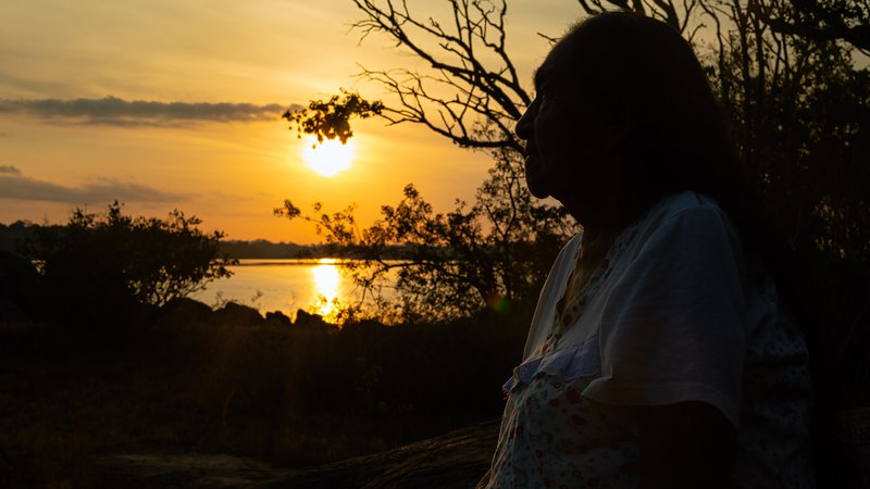 Odete Kuruayade in profile in front of a lake during sunset