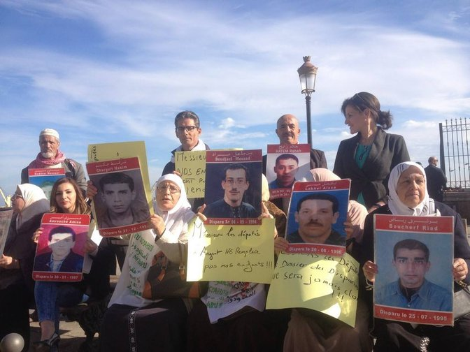 Algerian women hold up posters featuring photos of relatives who have disappeared, 2015.