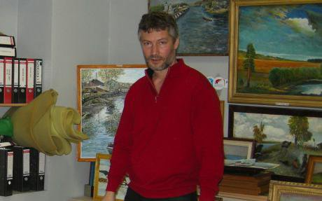 Roizman stands in his office in front of several paintings.