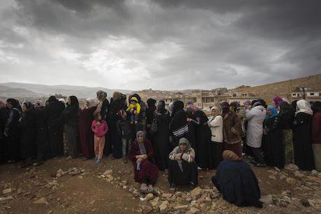A line of female refugees from Syria waits to register with UNHCR in Arsal, Lebanon, November 2013. M. Hofer/UNHCR/Flickr. Som
