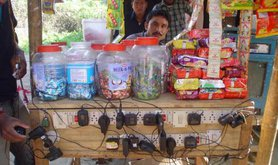 A shopkeeper charging mobile phones in the village of Gohpur, Assam in India
