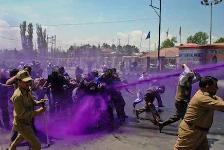 Indian police spray purple coloured water from water cannons at protesters. A jet of purple water directly hits some protesters