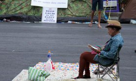 A Thai women sits peacefully in a chair in a street during a protest in Bangkok