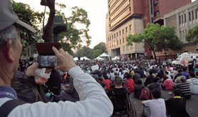 Elderly man uses his smartphone to video record the large crowd gathered on Jinan Road