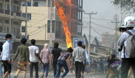 Ragged line of youths in a street facing off against line of soldiers. Fire in the air.