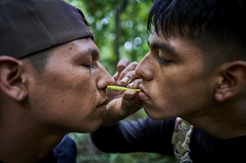 Bebeto, one of G.I.A.'s youngest, blows rapé on Christian's nose, one of his companions, during a routine tour. Rapé is a dust drawn from a mixture of tobacco and other medicinal plants, considered traditional medicine.