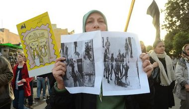 A protester holds pictures of a victim that was stripped by army forces in 2011. Demotix/Halim Elshaarani. Alll rights reserved.