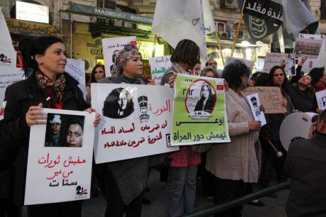 Demonstrators hold posters of women sexually harassed during mass protests.