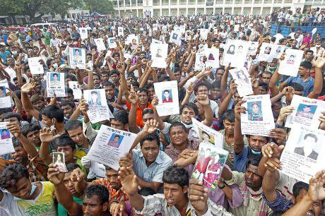 Relatives of the Savar tragedy victims hold the photos of their dear ones who still remain missing for the fifth day