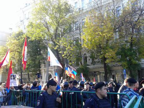 Counter-demonstrators, held back by a police cordon, hold flags of 'Novorossiya.'