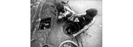 Cleaning drains (Photo © Sudharak Olwe 2003)