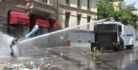 A man with a flag is directly hit by a stream of water from a police water cannon during Turky's Gezi Park protests