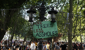 A mass of people fading in background with 'more trees less assholes' banner at forefront.