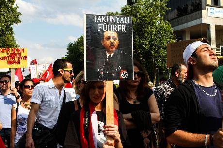 A picture of Turkish PM Recep Tayyip Erdogan dressed as a Nazi is seen as protesters stage a demonstration in Berlin