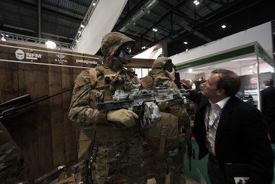 A visitor inspects soldiers wearing camouflage suits at the DSEI arms fair in London, 2013.