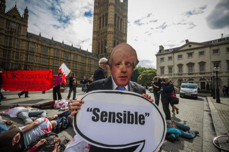 Protestors against the arms trade mimic Boris Johnson outside Parliament