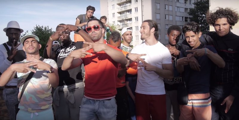 "Ademo (orange T-shirt) and N.O.S (white T-shirt) and their entourage forming with their hands a ""Z"" signifying ""le zoo"", to describe their hood, Les Tarterêts, in the 2015 debut single Le monde ou rien (The world or nothing) viewed over 100 million times"