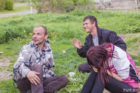 Oleg sits on the ground with two other people. They have an empty bottle in between them.