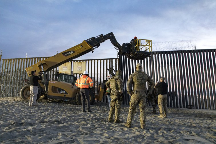 US border patrol stands watch as barbed wire is added to a border wall, 2018.