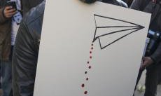 Protester at anti-drone demo in London with graphic image of how drones kill