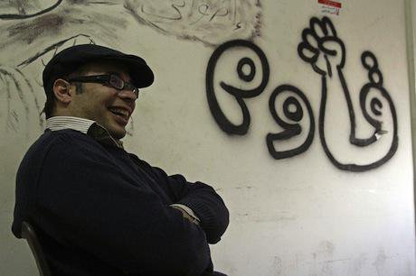 Ahmed Maher next to a graffito saying 'resist'. Demotix/Roger Anis. ALl rights reserved.