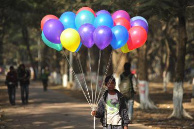 A 10 year old Bangladeshi migrant child selling ballons to earn money for his climate change refugee family