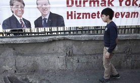 Boy walks past an election poster featuring Turkish PM Erdoğan