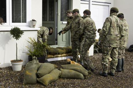 The army in front of a flooded house in Surrey