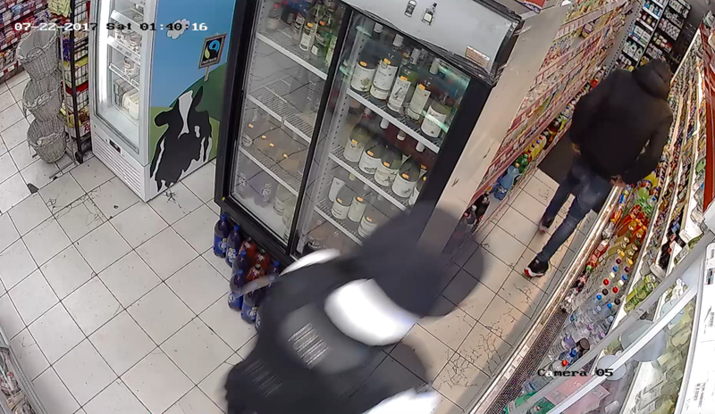 Police officer walking into shop, young man is in the shop ahead of him.