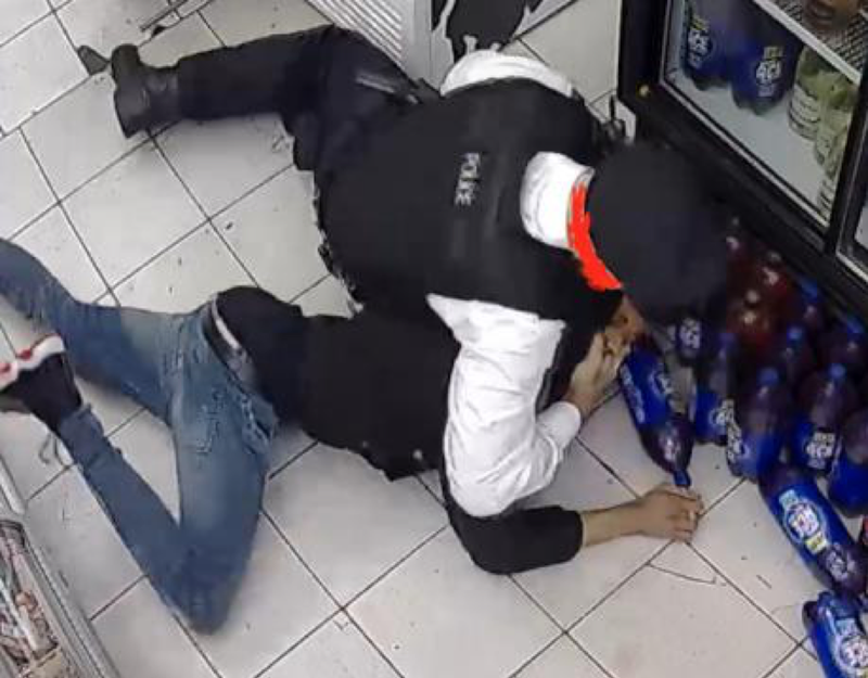 Policeman holds young man on ground of convenience shop