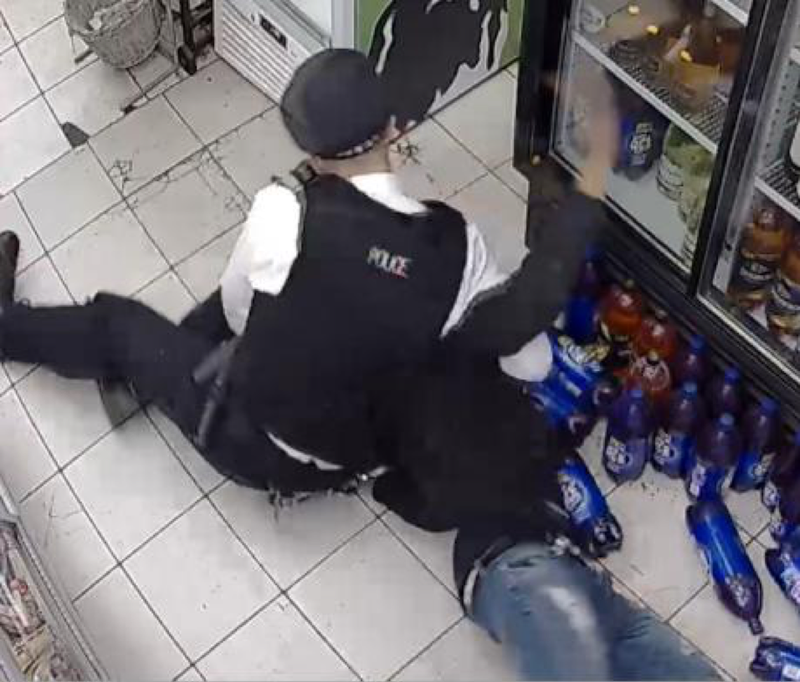 Police officer holds young man, their faces are obscured. The young man's hand taps a drinks fridge. They are inside a small shop.
