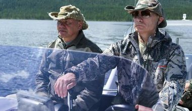 Shoigu and Putin in camouflage gear in a small fishing boat.