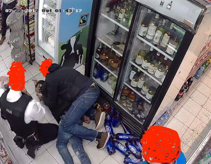 Rashan lying on the shop floor, held down by man in hoody and police kneels by his side.