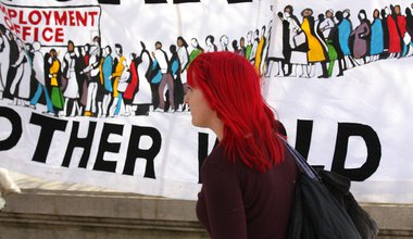 A woman walks past an anti-austerity placard on the Southbank.