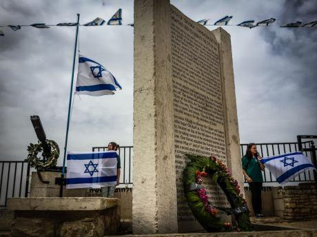 Israeli youth in northern Galilee hold flags at attention near a memorial to casualties in the Israe