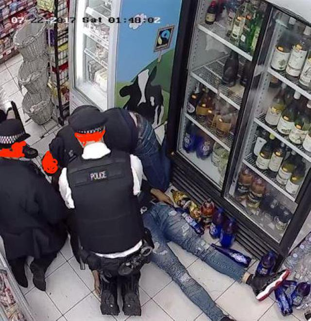 Two police officers and man lean over young man lying still on the floor.