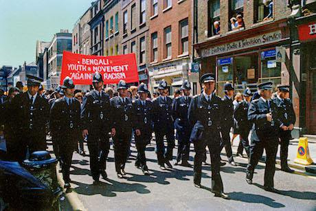 Police officers line up in front of protestors on Brick Lane