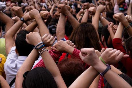 A group of people raising their hands in Barcelona.