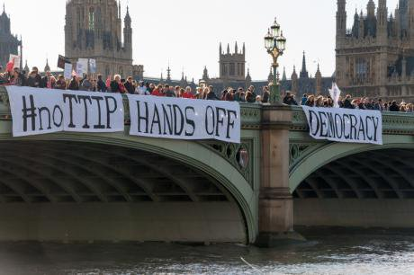 Banner drop protest at EU-US trade deal off Westminster Bridge, Oct.2014.