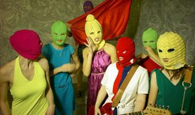 The 6 members of Pussy Riot pose with a guitar and colourful knitted masks on their heads.