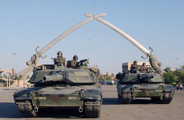 "US tanks pose in front of the ""Hands of Victory"" monument, Baghdad, 2003. Wikimedia Commons/Public Domain."