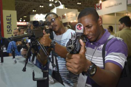 Two men holding guns in the LAAD Defence and Security Fair 2015, Rio de Janeiro.