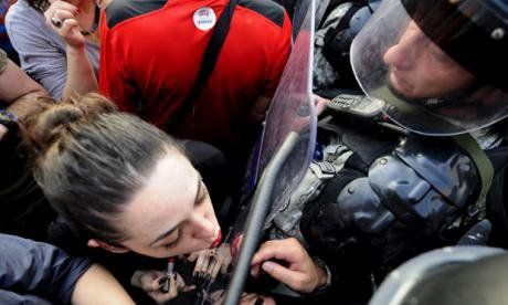 Woman applies lipstick in riot shield in Macedonia