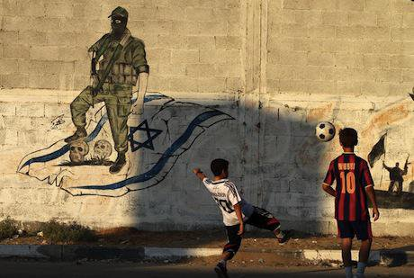 Palestinian boys play football in front of anti-Israel graffiti, Gaza City, 2011. Demotix/Majdi Fathi. All rights reserved.