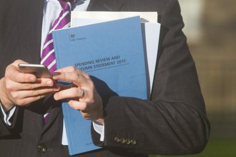 An MP holds the 2015 Autumn statement spending review booklet.
