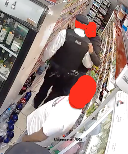 Man in hoody places hand on the back of a second man who is a police officer