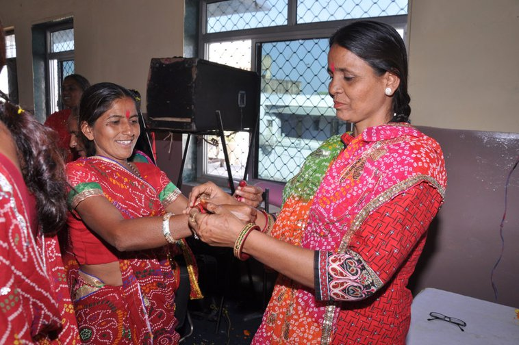Women of ASWA tying threads around one another's wrists during the Behen Dooj festival to represent group solidarity
