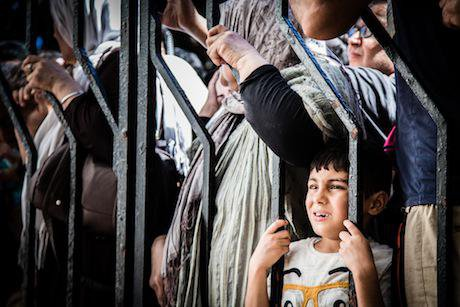 A boy from Iraq stands with his family at the gate of the registration centre in Kos. Stephen Ryan:Flickr. Some rights reserved.jpg